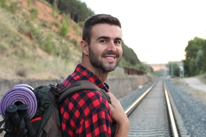 Young guy waiting for the train in station with smile and happy, single alone man at train station with back pack for travel royalty free stock image