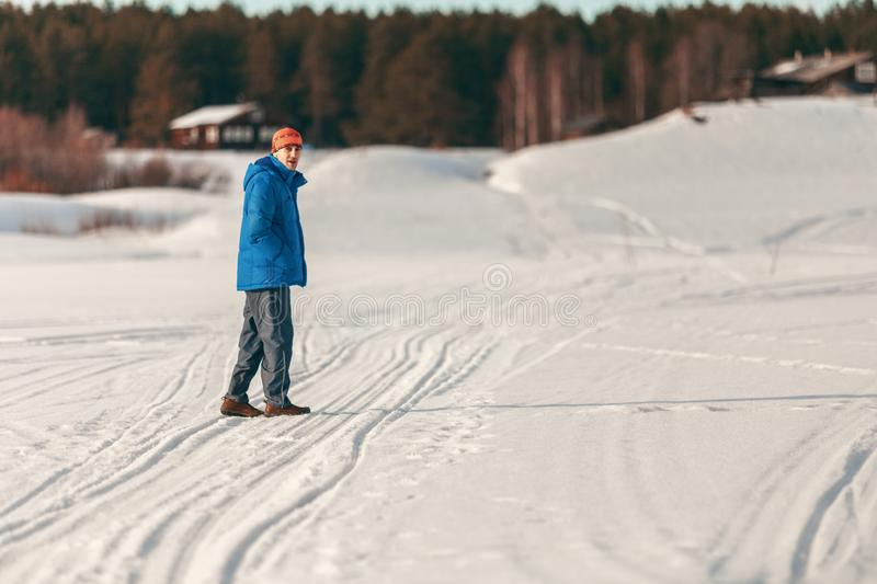 Young guy in warm clothes walking in the winter in the countryside stock photo