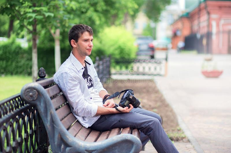 The young guy in a white shirt sits on a shop on the street in the park, holds the mirror camera in hand stock photo