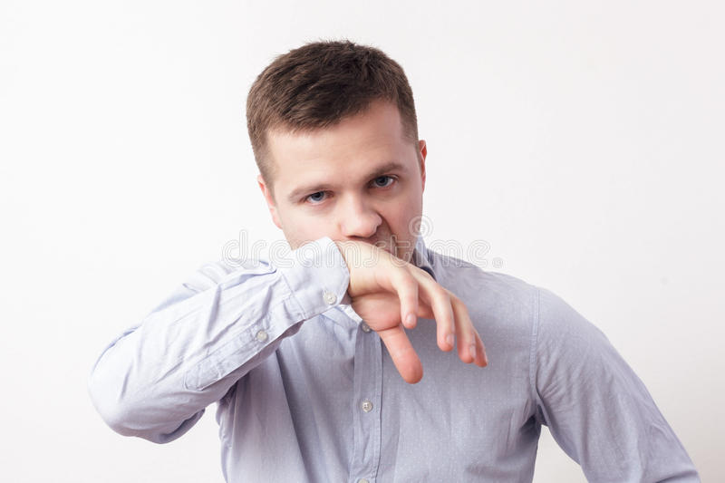 Caucasian man in bad mood. Young guy wipes blood and snot with sleeve stock images