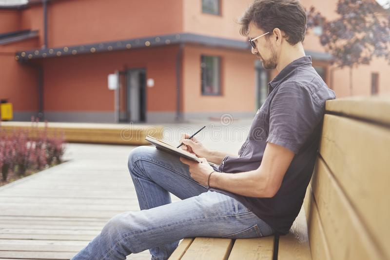 Young guy writing in a note book sitting outside. Man wearing glasses alone concentrated. Concept of education students youth stock image