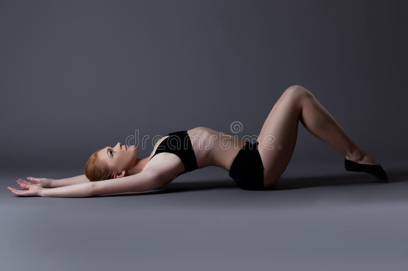 Young Gymnast Girl In Black Top Lay On Background Royalty Free Stock Photo