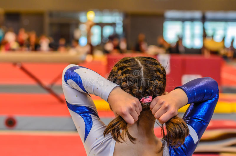 Young gymnast girl fixing hair before appearance royalty free stock image