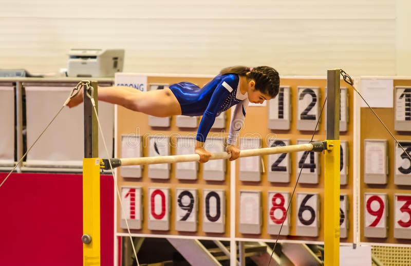 Young gymnast girl performing routine on high bar royalty free stock photo