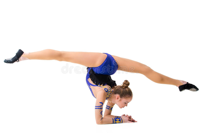 Young gymnast on a white background. Sporting exercises. Aerobics. Flexibility. Plastic study. Twine royalty free stock image