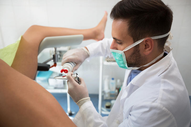 Young gynecologist putting gel on equipment to exam patient. Young male gynecologist putting gel on equipment to exam patient royalty free stock image