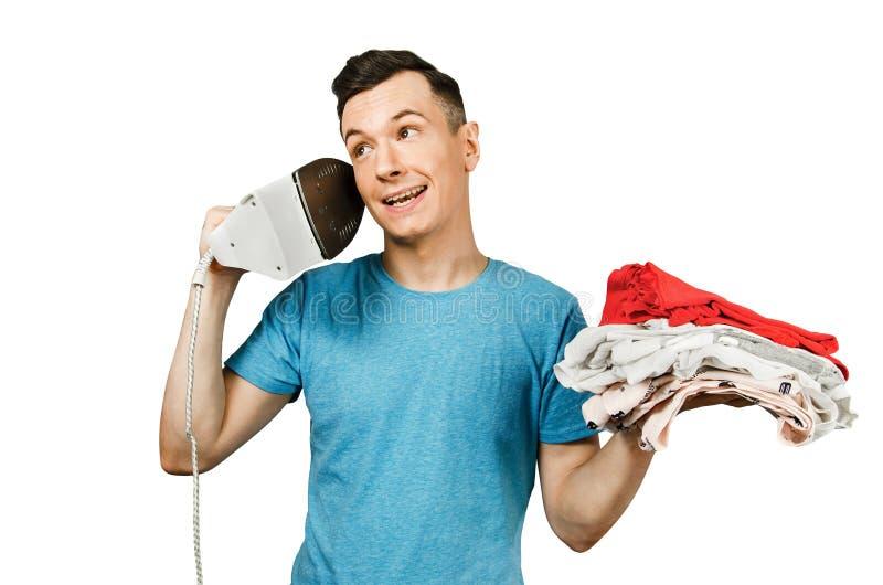 Young gyu fala sobre o ferro como no telefone em um fundo cinza claro imagens de stock royalty free