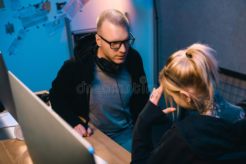 Young hacker talking with depressed accomplice at workplace. In dark room royalty free stock image
