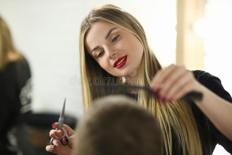 Young Hairdresser Cutting Male in Beauty Salon stock photo