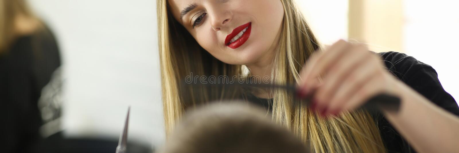 Young Hairdresser Cutting Male in Beauty Salon. Woman Hairstylist with Scissors and Hairbrush Styling Haircut for Client. Professional Beautician Combing Guy stock photo
