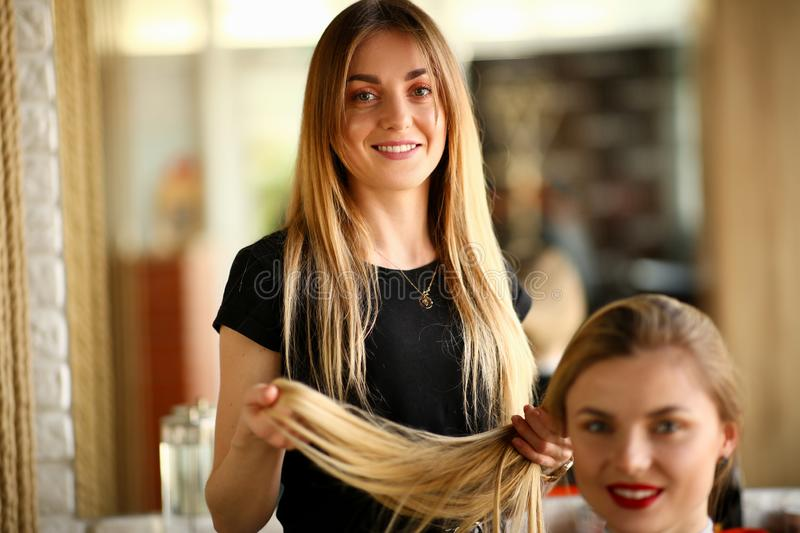 Young Hairdresser Holding Hair of Female Client. Smiling Hairstylist Picking Haircut for Girl. Two Blonde Woman in Beauty Salon. Stylist Beautician Styling stock images