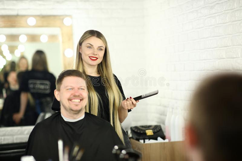 Young Hairdresser with Man Client in Beauty Salon royalty free stock photography