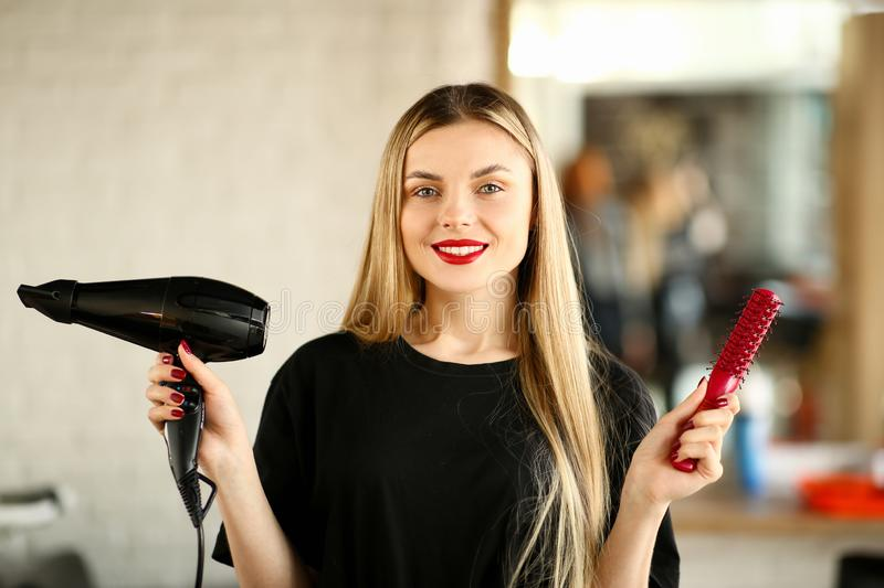 Young Hairstylist Holding Blow Dryer and Hairbrush. Blonde Hairdresser Showing Hairdryer and Red Comb for Haircut Styling. Stylist Using Professional Equipment royalty free stock photos
