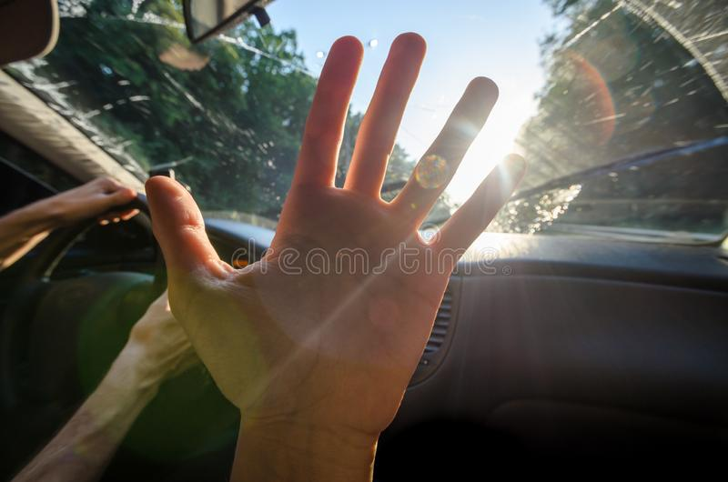 Young hand against the sun in the car with highlights royalty free stock photo