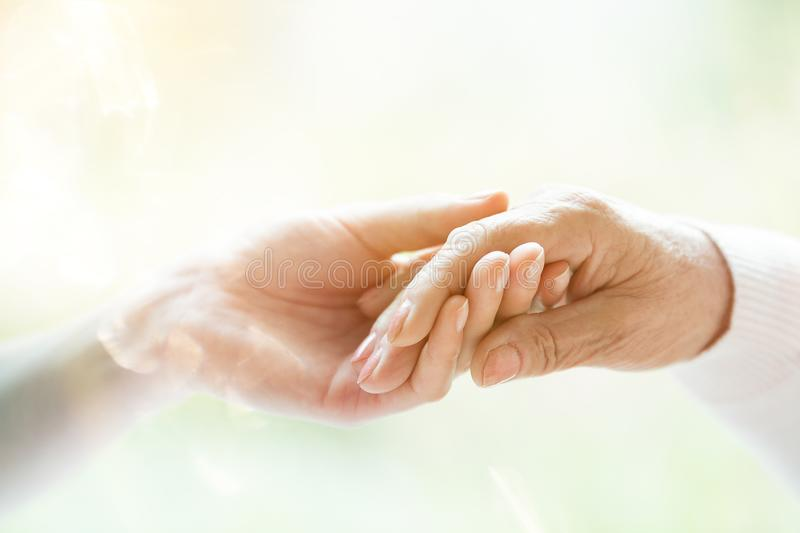 Young hand holding elderly hand stock image
