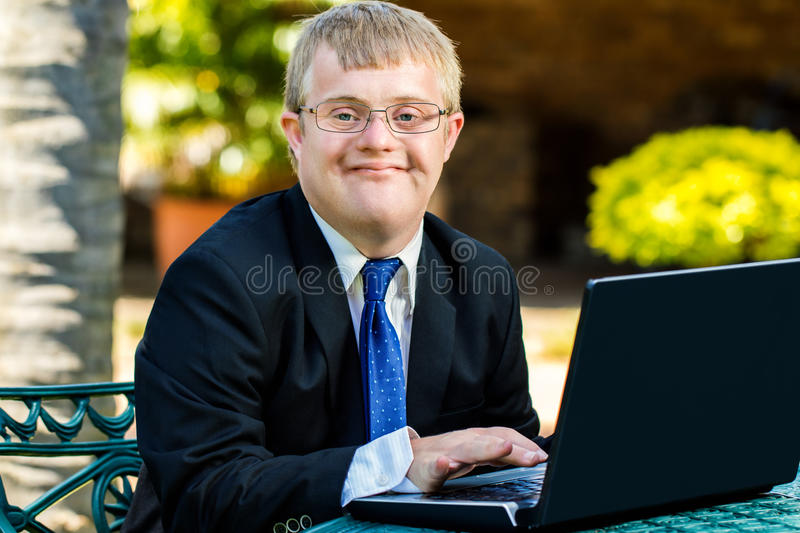 Young handicapped businessman working with laptop. stock image
