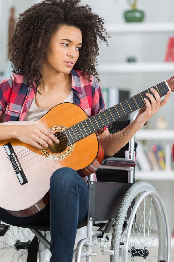 Young handicapped guitarist woman sitting on wheelchair. Woman stock photo
