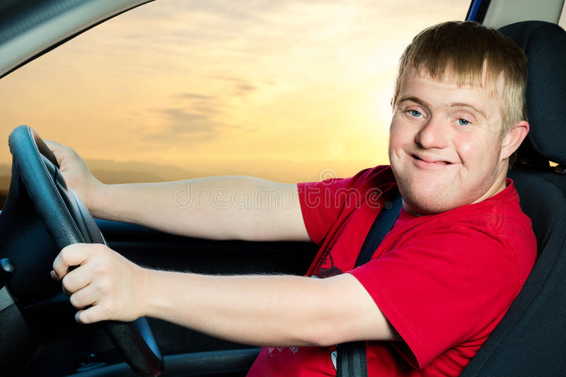 Young handicapped man driving car. Close up portrait of young man with down syndrome driving vehicle at sunset royalty free stock images