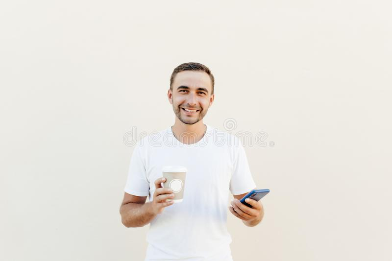 Young handsom man in casual wear checking news on smartphone while holding takeaway coffee, isolated on pastel background stock image