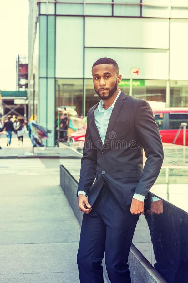 Young Handsome African American Man with beard travel in New York. Wearing black jacket, pants, white undershirt, standing on street in Middletown of Manhattan stock image