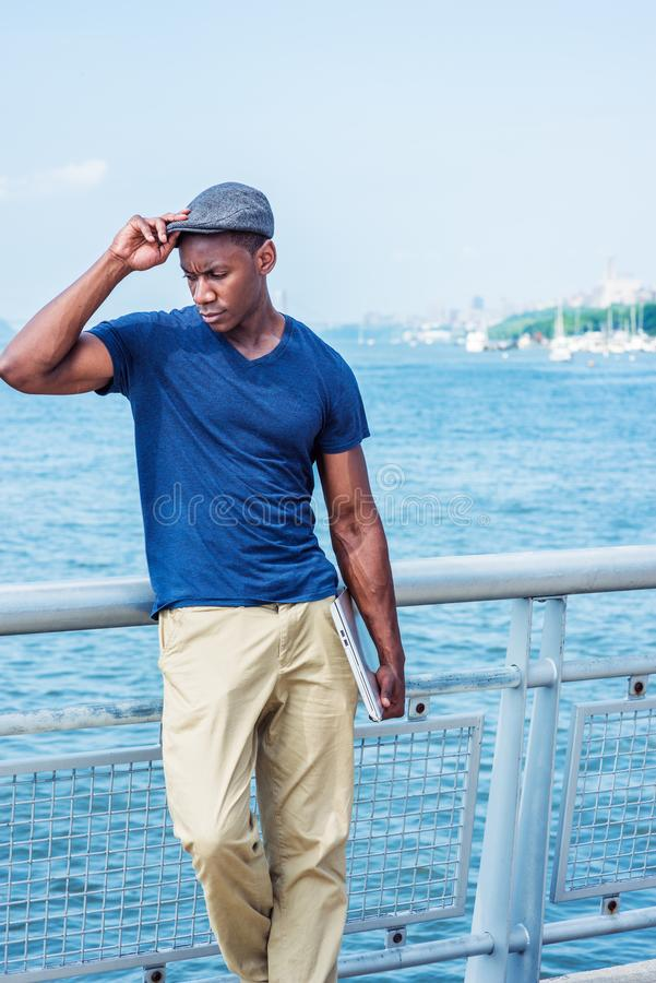 Young Handsome African American Man in New York. Wearing blue V neck T shirt, beige pants, flat cap, carrying laptop computer, standing by Hudson River, hand stock photos