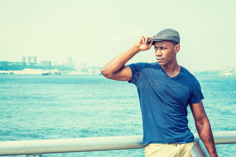 Young Handsome African American Man traveling in New York. Wearing blue V neck T shirt, flat cap, carrying laptop computer, standing by Hudson River, hand stock images