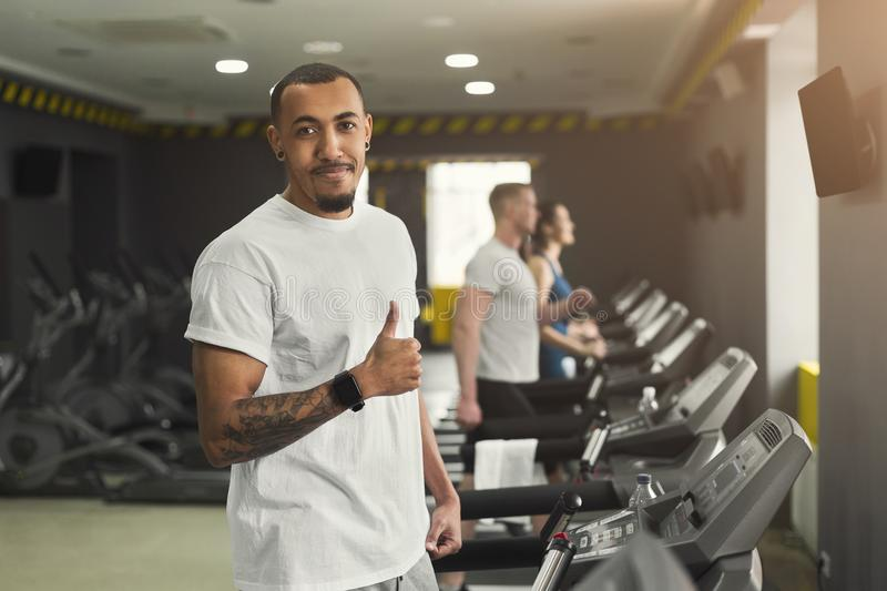 Young black man in gym running on treadmill stock image