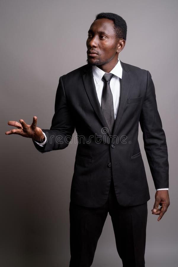Young handsome African businessman against gray background. Studio shot of young handsome African businessman against gray background stock photos