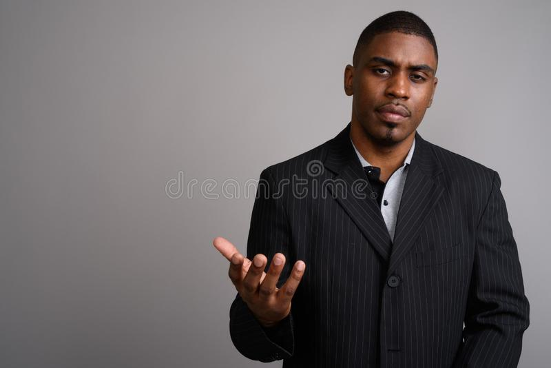 Young handsome African businessman wearing suit against gray bac. Studio shot of young handsome African businessman wearing suit against gray background stock photos