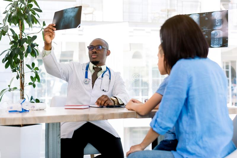 Young handsome African male Doctor In Surgery Examining x-ray of Young boy, coming with his mom to modern clinic royalty free stock images