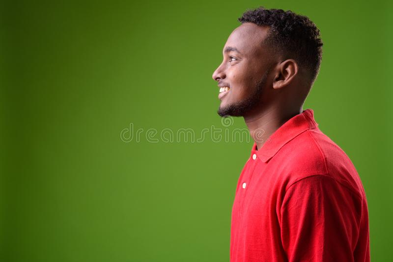 Young handsome African man against green background royalty free stock image