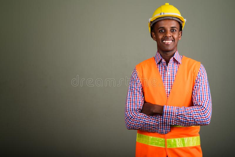 Young handsome African man construction worker against colored b royalty free stock photos