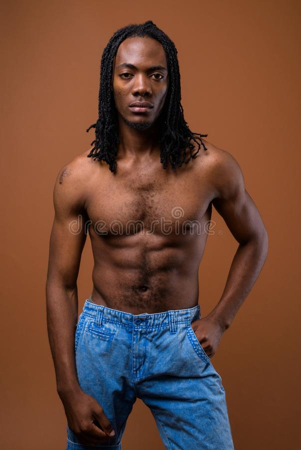Young handsome African man shirtless against brown background royalty free stock photo