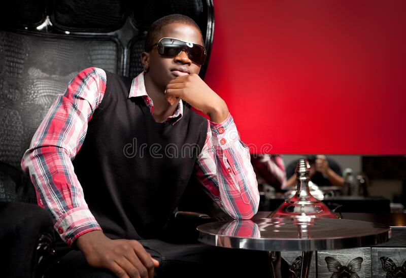 Young handsome african man in stylish casual clothing and sunglasses sitting in big black leather armchair in restaurant royalty free stock photos