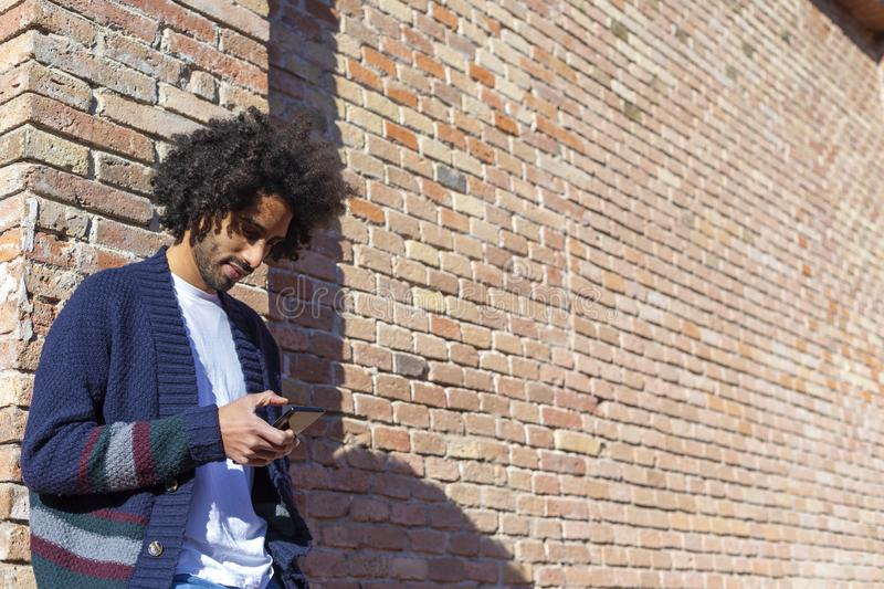 Young handsome African man using his smartphone with smile while leaning on a bricked wall outdoors in sunny day royalty free stock photography