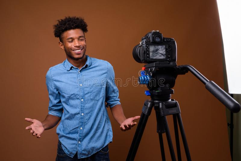 Young handsome African man vlogging with DSLR camera in studio. Studio shot of young handsome African man wearing smart casual clothing against brown background royalty free stock photo