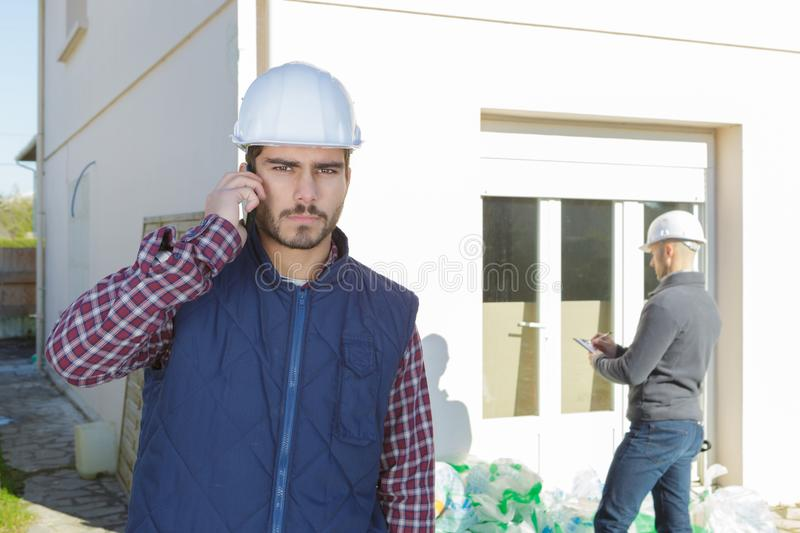 Young handsome architect supervising construction using cell phone outdoors stock image