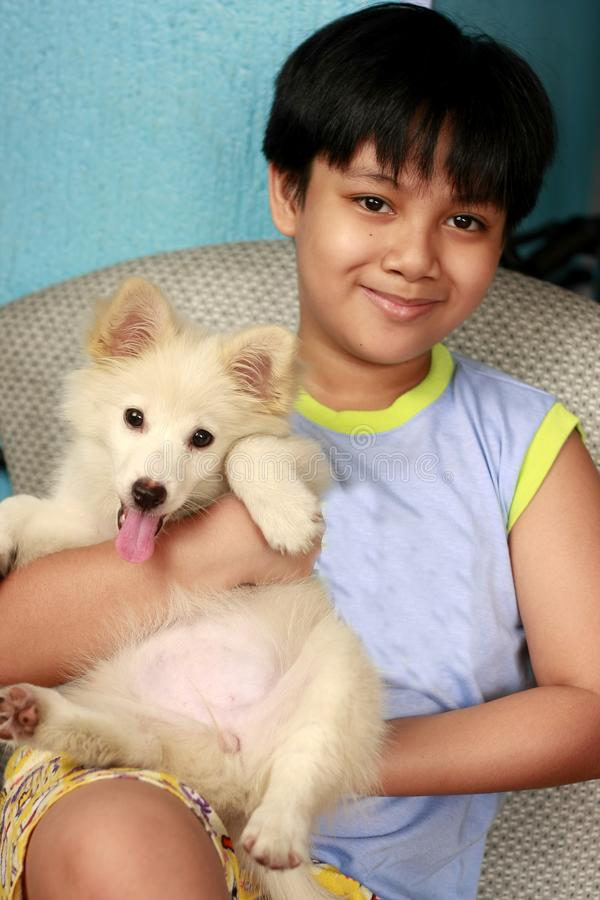 Young handsome Asian boy carrying a cute white puppy. Portrait of a young handsome Asian boy carrying a cute white puppy stock photography