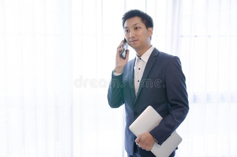 Young handsome asian business man in blue jacket suit, business style, white shirt, isolated, white background, smiling, standing royalty free stock photography