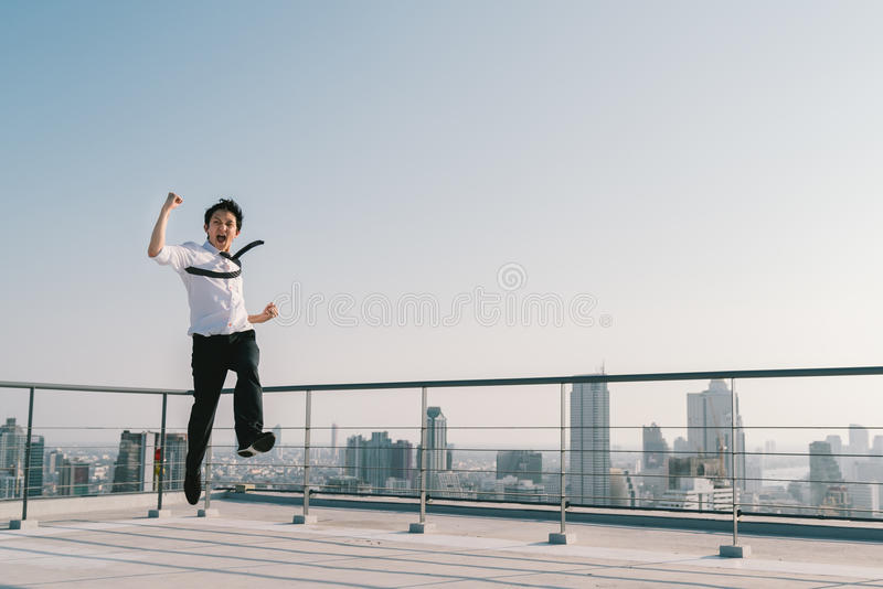 Young handsome Asian businessman jumping celebrate success winning pose on building roof. Work, job, or success concept. Young handsome Asian businessman jumping royalty free stock photography