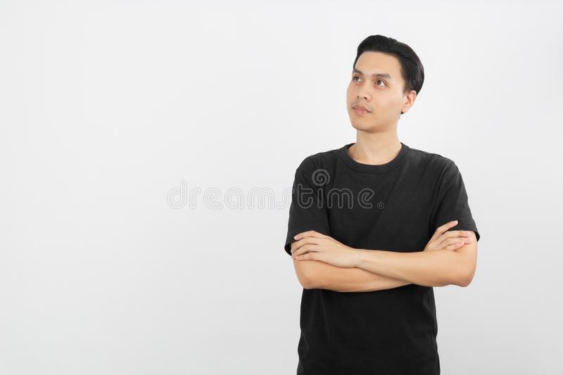 Young handsome asian man thinking an idea while looking up with arms crossed isolated on white background. stock photography