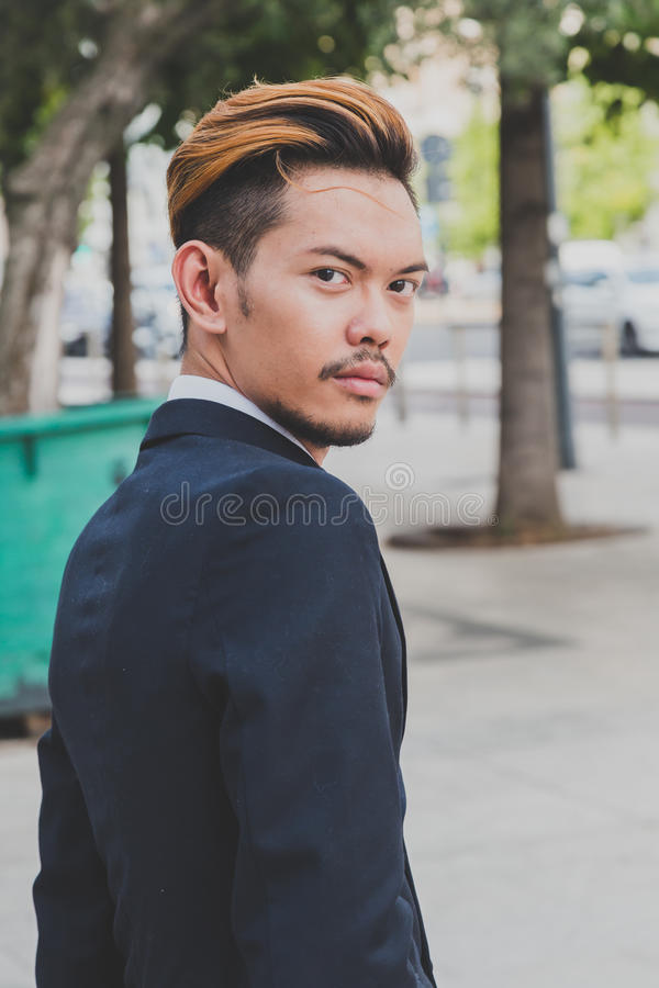 Young handsome Asian model posing in the city streets stock image
