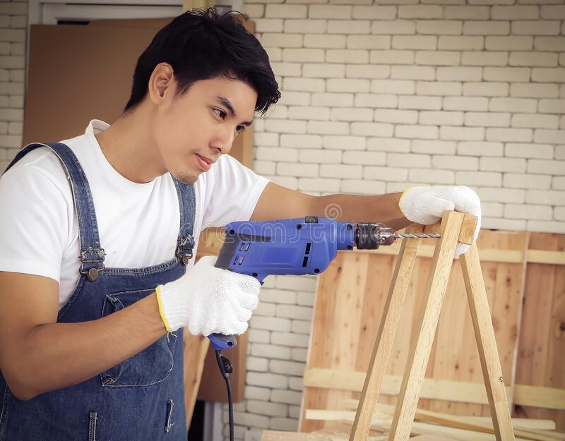 Handsome Asian repairman standing in wood workshop with white brick wall , holding drill in working with wooden frame stock image