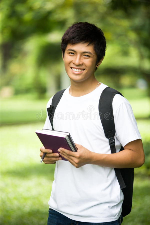 Young handsome Asian student with books and smile in outdoor royalty free stock image