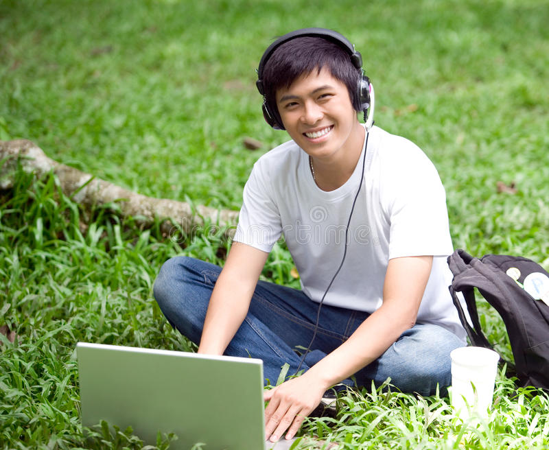 Young handsome Asian student with laptop and smile in outdoor royalty free stock photography