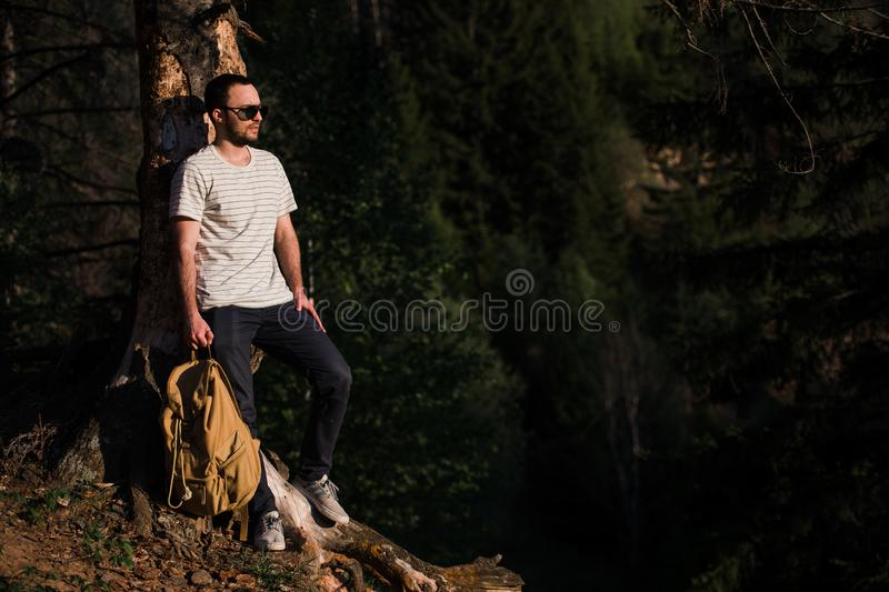 Young handsome attractive bearded model man with backpack in the woods posing near tree. royalty free stock photography