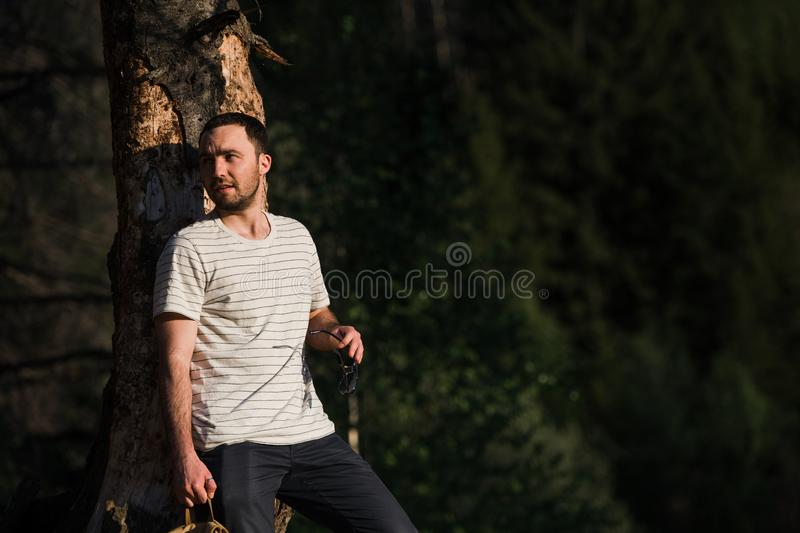 Young handsome attractive bearded model man with backpack in the woods posing near tree. royalty free stock image