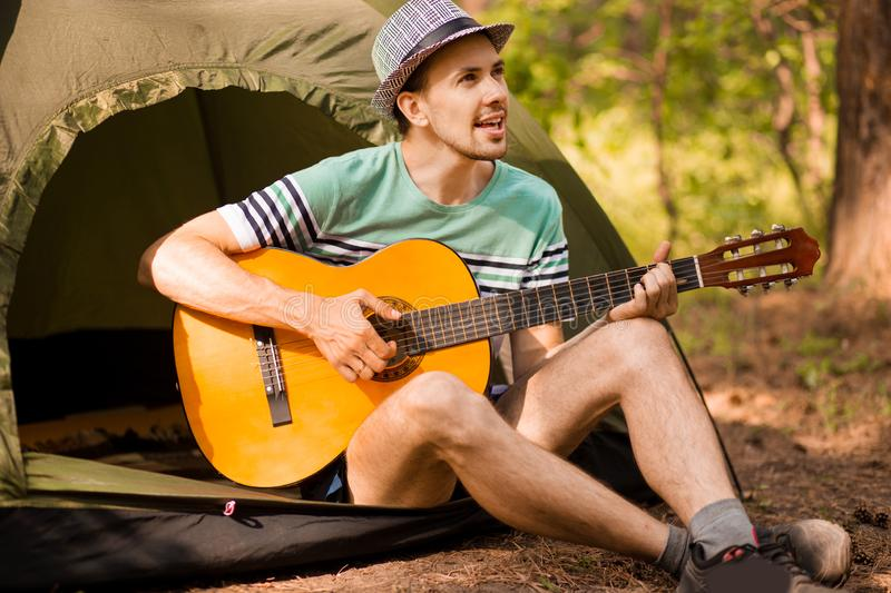 Young handsome attractive bearded model man in hat playing guitar in forest. stock photo