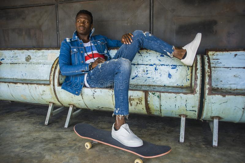 Young handsome and attractive black African American skateboarder man sitting on city grunge bench holding skate board posing in. Urban lifestyle portrait of stock photography