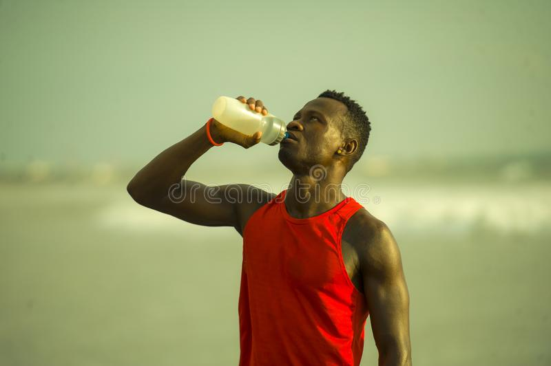Young handsome and attractive black African American sport man tired and thirsty after running workout holding bottle drinking. Water or isotonic energy drink royalty free stock photo
